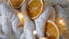 Ξηρές πορτοκαλιές φέτες, ντεκόρ Χριστουγέννων άσπρο καρό με μια γιρλάντα Κινηματογράφηση σε πρώτο πλάνο φιλμ μικρού μήκους