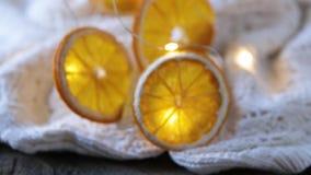 Ξηρές πορτοκαλιές φέτες, ντεκόρ Χριστουγέννων άσπρο καρό με μια γιρλάντα Κινηματογράφηση σε πρώτο πλάνο απόθεμα βίντεο
