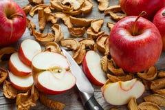 Ξηρές φέτες μήλων και κόκκινα φρέσκα κόκκινα φρούτα μήλων στην παλαιά κουζίνα Στοκ Εικόνα