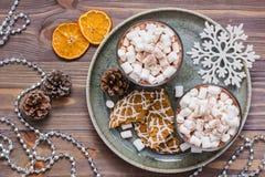 Ξηρές φέτες μανταρινιών, καυτό κακάο με marshmallows και τα μπισκότα Χριστουγέννων στον πίνακα στις διακοσμήσεις Χριστουγέννων στοκ φωτογραφίες