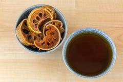 Ξηραμένα από τον ήλιο φρούτα Bael στο κύπελλο δίπλα στο φλυτζάνι του καυτού βοτανικού τσαγιού Bael, Στοκ Φωτογραφία