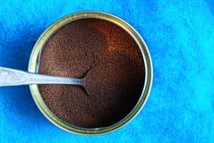 Ξηρός καφετής στιγμιαίος καφές σε ένα βάζο μετάλλων με ένα κουτάλι σε ένα μπλε υπόβαθρο στοκ φωτογραφία με δικαίωμα ελεύθερης χρήσης