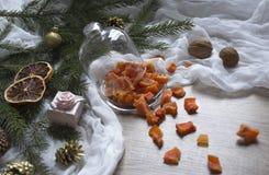 Ξηρός - τα πορτοκαλιά γλασαρισμένα φρούτα ανανά κολοκύθας φρούτων σε έναν πίνακα κάτω από ένα χριστουγεννιάτικο δέντρο γυαλιού ΚΑ Στοκ Φωτογραφία