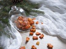 Ξηρός - τα πορτοκαλιά γλασαρισμένα φρούτα ανανά κολοκύθας φρούτων σε έναν πίνακα κάτω από ένα χριστουγεννιάτικο δέντρο γυαλιού ΚΑ Στοκ Εικόνα