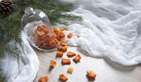 Ξηρός - τα πορτοκαλιά γλασαρισμένα φρούτα ανανά κολοκύθας φρούτων σε έναν πίνακα κάτω από ένα χριστουγεννιάτικο δέντρο γυαλιού ΚΑ Στοκ Εικόνες