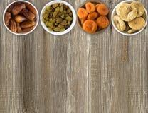 Ξηρός - φρούτα ξύλινα κύπελλα Σταφίδες, ημερομηνίες, ξηρά βερίκοκα, σύκα σε ένα ξύλινο υπόβαθρο Στοκ εικόνα με δικαίωμα ελεύθερης χρήσης