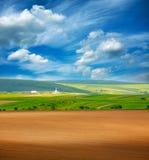 Ξηρό οργωμένο γήινο γεωργικό πράσινο καλλιεργήσιμο έδαφος χώρας στο μπλε ουρανό Στοκ φωτογραφία με δικαίωμα ελεύθερης χρήσης