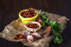 Ξηρό πιπέρι, τμήματα σκόρδου και μαϊντανός στην πετσέτα Στοκ Φωτογραφίες