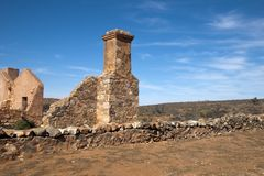 Ξηρό τοπίο με το εγκαταλειμμένο σπίτι και καπνοδόχος στο πρώτο πλάνο στοκ φωτογραφία με δικαίωμα ελεύθερης χρήσης