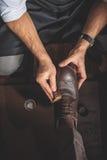 Ξοντρά παπούτσεις δέρματος πλύσης ατόμων με ένα σφουγγάρι στοκ εικόνα