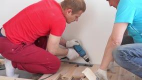Ξυλουργική στο σπίτι - δύο επαγγελματικά άτομα τοποθετούν το πάτωμα ξύλου πεύκων απόθεμα βίντεο