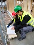 Ξυλουργοί που συζητούν πέρα από το σχέδιο στο εργοτάξιο οικοδομής Στοκ Εικόνες