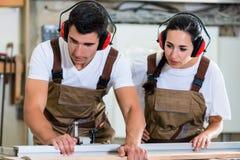 Ξυλουργός και μαθητευόμενος που εργάζονται μαζί στο εργαστήριο Στοκ Εικόνες