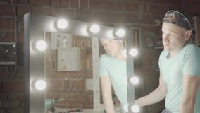 Ξυλουργός πορτρέτου που ελέγχει τον καθρέφτη με τα φω'τα εάν η εργασία του ή όχι εργασία Κατασκευή χεριών Εργασίες Craftman σε έν απόθεμα βίντεο