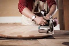 Ξυλουργός που αλέθει τον ξύλινο πίνακα Στοκ Φωτογραφίες
