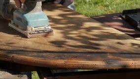 Ξυλουργός που αποκαθιστά τα παλαιά έπιπλα, λείανση παλαιό ξύλινο countertop κίνηση αργή φιλμ μικρού μήκους