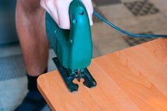 Ξυλουργός που εργάζεται με ένα τορνευτικό πριόνι και ένα ξύλινο τέμνον εγχειρίδιο τορνευτικών πριονιών Στοκ Εικόνες