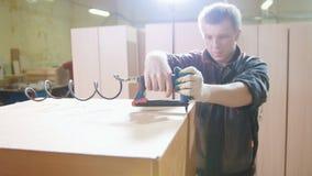 Ξυλουργός που εργάζεται με ηλεκτρικό βιομηχανικό stapler στο εργοστάσιο, καθορίζοντας λεπτομέρειες επίπλων, κινηματογράφηση σε πρ Στοκ εικόνα με δικαίωμα ελεύθερης χρήσης