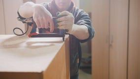 Ξυλουργός που εργάζεται με ηλεκτρικό βιομηχανικό stapler στο εργοστάσιο, καθορίζοντας λεπτομέρειες επίπλων Στοκ φωτογραφία με δικαίωμα ελεύθερης χρήσης