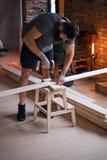 Ξυλουργός που τρυπά μια τρύπα σε έναν πίνακα σε ένα δωμάτιο με το interio σοφιτών με τρυπάνι Στοκ φωτογραφία με δικαίωμα ελεύθερης χρήσης