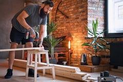 Ξυλουργός που τρυπά μια τρύπα σε έναν πίνακα σε ένα δωμάτιο με το interio σοφιτών με τρυπάνι Στοκ φωτογραφίες με δικαίωμα ελεύθερης χρήσης