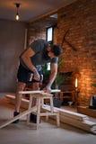 Ξυλουργός που τρυπά μια τρύπα σε έναν πίνακα σε ένα δωμάτιο με το interio σοφιτών με τρυπάνι Στοκ Φωτογραφία