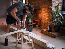 Ξυλουργός που τρυπά μια τρύπα σε έναν πίνακα σε ένα δωμάτιο με το interio σοφιτών με τρυπάνι Στοκ εικόνα με δικαίωμα ελεύθερης χρήσης