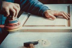ξυλουργός που χρησιμοποιεί sander για τα ξύλινα έπιπλα Στοκ φωτογραφία με δικαίωμα ελεύθερης χρήσης