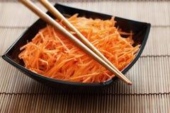 Ξυμένα καρότα στο κύπελλο με chopsticks Στοκ φωτογραφία με δικαίωμα ελεύθερης χρήσης