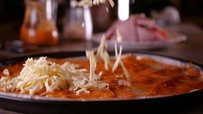 Ξυμένη πτώση τυριών στην πίτσα με τη σάλτσα στο τηγάνι ψησίματος απόθεμα βίντεο