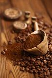 Ξυμένος καφές στο κουτάλι στο ψημένο υπόβαθρο φασολιών καφέ Στοκ Φωτογραφία