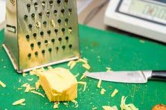 Ξυμένο τυρί με τον ξύστη και το μαχαίρι στοκ εικόνες