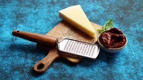 Ξυμένο τυρί παρμεζάνας και κλασικός ξύστης μετάλλων που τοποθετείται στον ξύλινο τέμνοντα πίνακα απόθεμα βίντεο