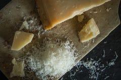Ξυμένο τυρί παρμεζάνας στο μαύρο υπόβαθρο, ιταλικά τρόφιμα στοκ εικόνες