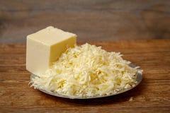 Ξυμένο τυρί στο μεταλλικό πιάτο στον ξύλινο πίνακα στοκ φωτογραφίες