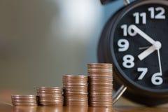 Ξυπνητήρι και βήμα των σωρών νομισμάτων στο λειτουργώντας πίνακα, χρόνος για Στοκ Εικόνες