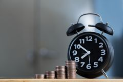 Ξυπνητήρι και βήμα των σωρών νομισμάτων στο λειτουργώντας πίνακα, χρόνος για Στοκ εικόνα με δικαίωμα ελεύθερης χρήσης