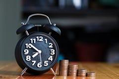 Ξυπνητήρι και βήμα των σωρών νομισμάτων στο λειτουργώντας πίνακα, χρόνος για Στοκ φωτογραφίες με δικαίωμα ελεύθερης χρήσης