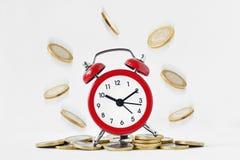 Ξυπνητήρι με τα μειωμένα νομίσματα στο άσπρο υπόβαθρο - ο χρόνος είναι mon στοκ φωτογραφίες