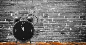 Ξυπνητήρι με τα μικρά πρακτικά στο ρολόι δώδεκα ο ` Στοκ Εικόνες