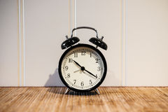 Ξυπνητήρι με το ρολόι 10 Ο ` και το μενουέτο είκοσι, στον ξύλινο πίνακα και τον άσπρο τοίχο Στοκ φωτογραφία με δικαίωμα ελεύθερης χρήσης