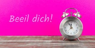ξυπνητήρι με το ρόδινο υπόβαθρο με το γερμανικό κείμενο beeil dich, στην αγγλική βιασύνη επάνω στοκ εικόνα με δικαίωμα ελεύθερης χρήσης