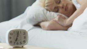 Ξυπνητήρι που στέκεται στο nightstand, ύπνος γυναικών στο κρεβάτι, άνεση στο σπίτι απόθεμα βίντεο