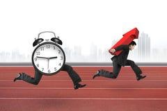 Ξυπνητήρι που τρέχει μετά από το άτομο που φέρνει το κόκκινο βέλος επάνω Στοκ Εικόνες