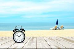 Ξυπνητήρι στην ξύλινη παραλία πινάκων και θάλασσας που θολώνεται στο υπόβαθρο Στοκ Εικόνες
