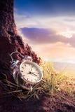 Ξυπνητήρι στη χλόη στη χρονική έννοια ηλιοβασιλέματος ή ανατολής Στοκ φωτογραφίες με δικαίωμα ελεύθερης χρήσης