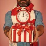 Ξυπνητήρι Χριστουγέννων στο παρόν κιβώτιο στα αρσενικά χέρια στοκ φωτογραφία με δικαίωμα ελεύθερης χρήσης