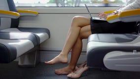Ξυπόλυτες εργασίες γυναικών με το lap-top στο τραίνο απόθεμα βίντεο