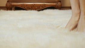 Ξυπόλυτες θηλυκές στάσεις στο μαλακό άσπρο τάπητα απόθεμα βίντεο