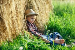 Ξυπόλυτο αγόρι στο καπέλο αχύρου που στηρίζεται στη θυμωνιά χόρτου Στοκ Εικόνα
